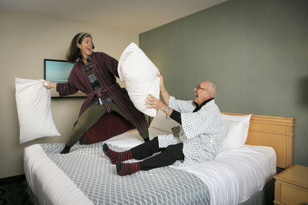 Mandy Farmer and her dad, Terry Farmer have a pillow fight on an Accent Inns bed