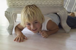 Small blonde child crawling under a living room chair