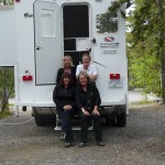 picture of Accent Inns sales team sitting by a camper for their northern trip